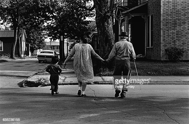 A blind Hispanic man crosses McClellan Street with his wife and son Fort Wayne Indiana