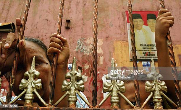 A blind Indonesian beggar and her son stand next to a mosque with an Amien Rais campaign poster in the backround July 2 in Indonesia Jakarta Voters...
