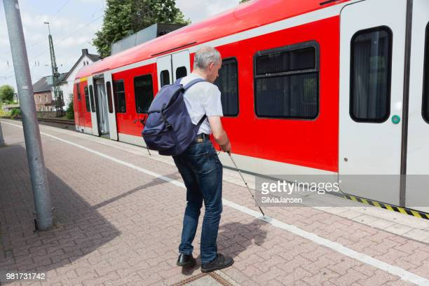 Blind man commuting with train