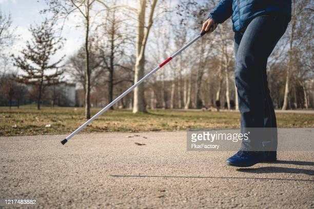 歩く杖の助けを借りて自分自身を導く盲目の男 - 白杖 ストックフォトと画像