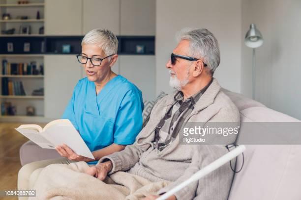 Homme aveugle écoute infirmière lu lui