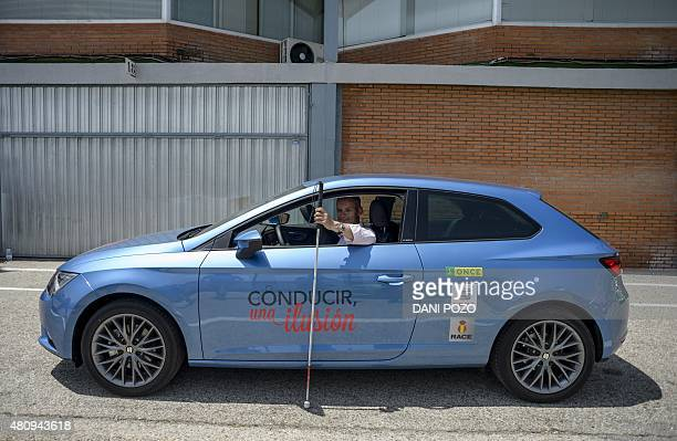 A blind man seated in a car shows his white stick before driving during the Master Drive experience To drive an illusion at the Jarama Circuit in...