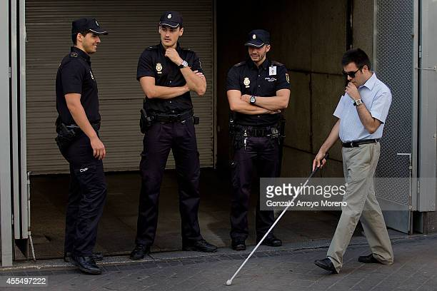 A blind man walks near police officers outside Spain's National Court during an appearance by Jordi Pujol Ferrusola before judge Pablo Ruz on...