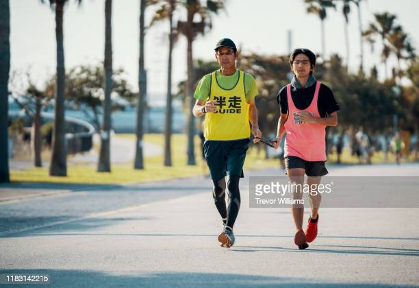 blind marathon athlete running with his guide - 障害者スポーツ ストックフォトと画像
