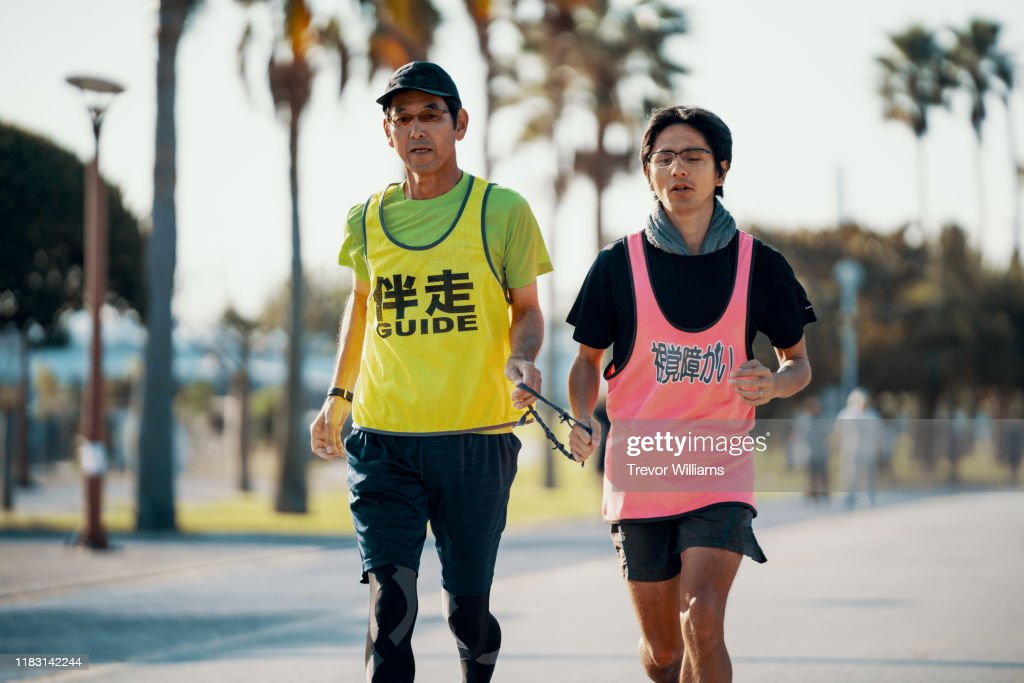 Blind marathon athlete running with his guide : Stock Photo
