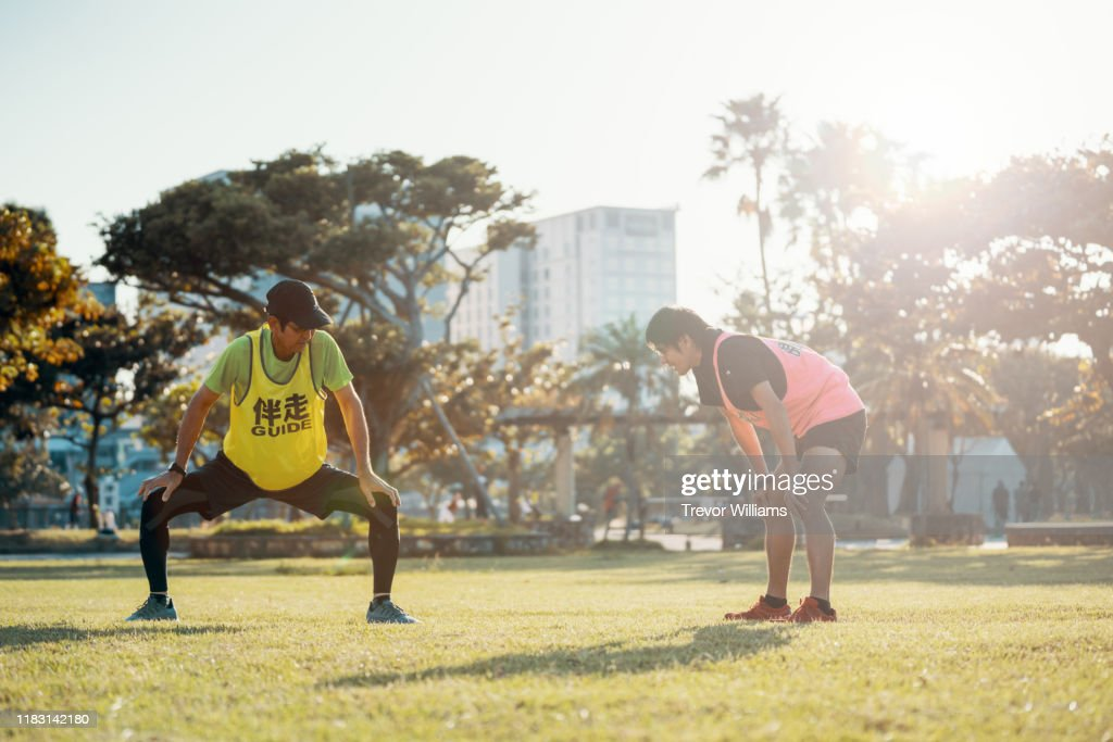Blind marathon athlete stretching and warming up with his guide before competing : ストックフォト