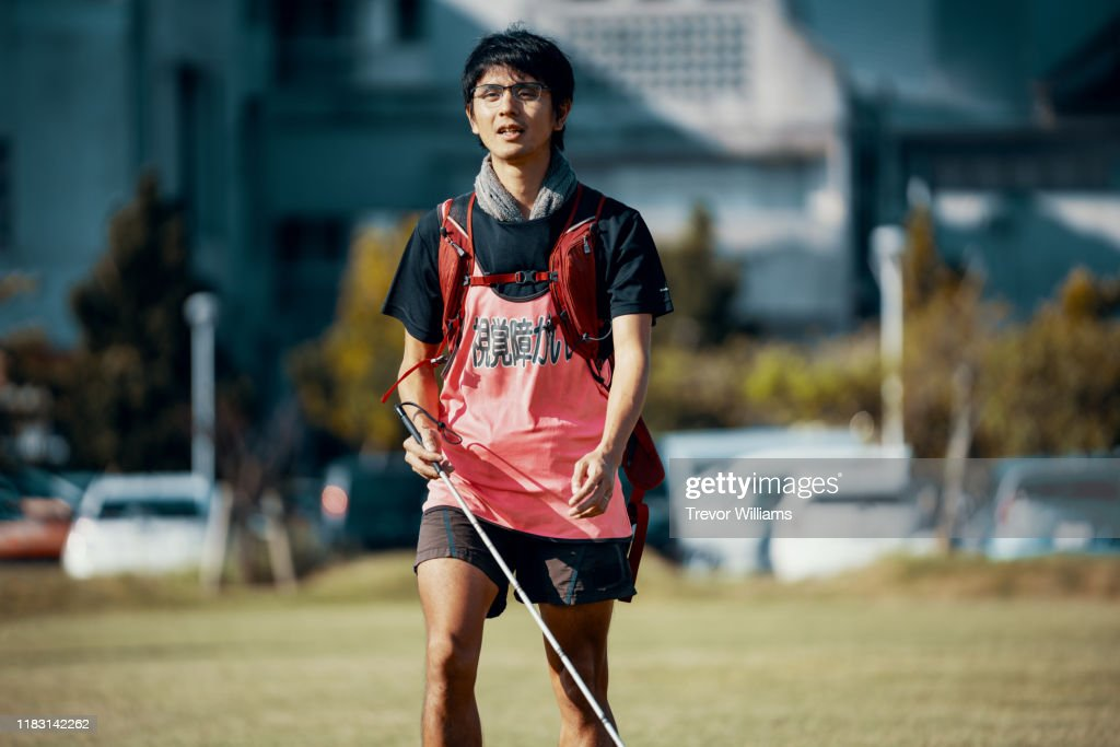 Blind marathon athlete walking with his white cane before competing : ストックフォト