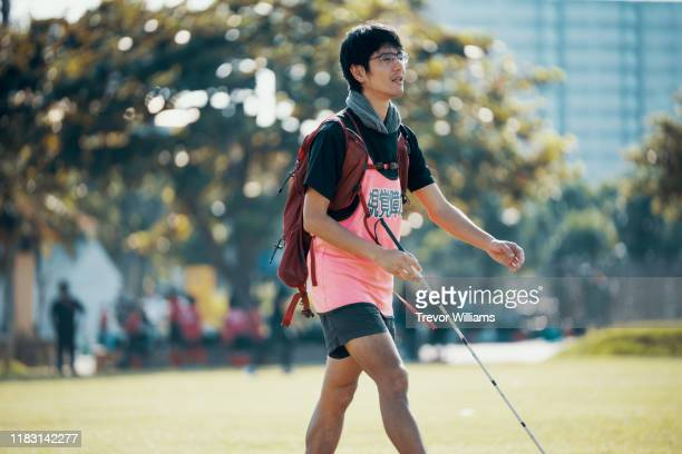 blind marathon athlete walking with his white cane before competing - persons with disabilities ストックフォトと画像