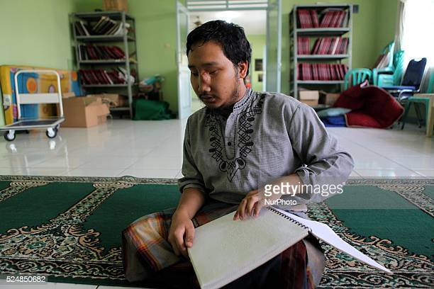 Blind men reads a Braille Quran at Raudlatul Makfufin Foundation in Tangerang outskrit of Jakarta Indonesia on June 24 2015 Braille Quran is the...