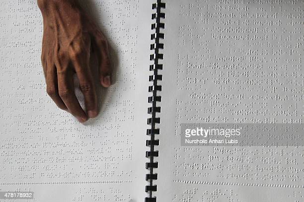 A blind reads a Braille Quran at a blind foundation on June 23 2015 in Tangerang Indonesia Braille Quran is the translation of Quran verses to...