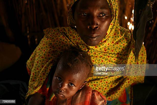 Blind Sudanese refugee Fathna Ibrahim who lost her husband and was tortured by members of Janjaweed sits with her daughter in a hut in the Goz Amir...