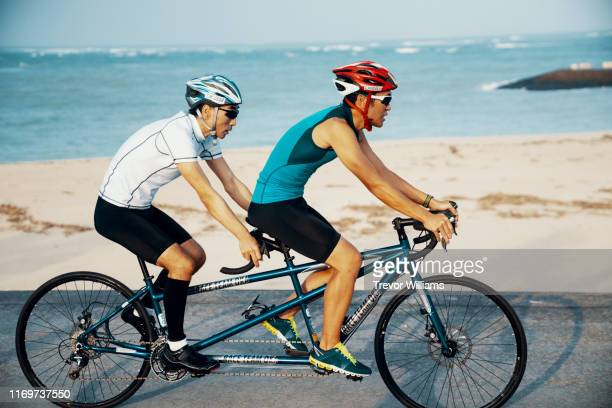 blind triathlete and his guide training on their tandem bicycle - 障害者スポーツ ストックフォトと画像