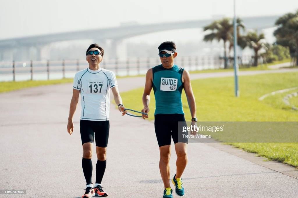 Blind triathlete and his guide walking before or after a triathlon event : ストックフォト