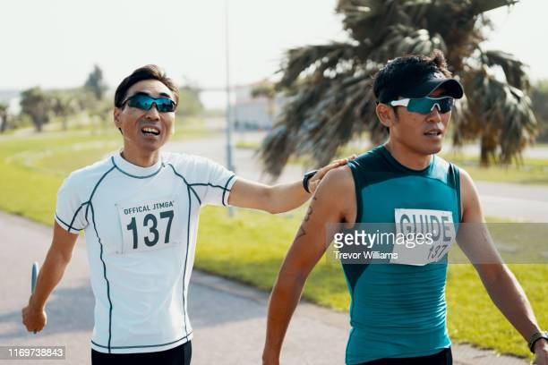 Blind triathlete and his guide walking before or after a triathlon event