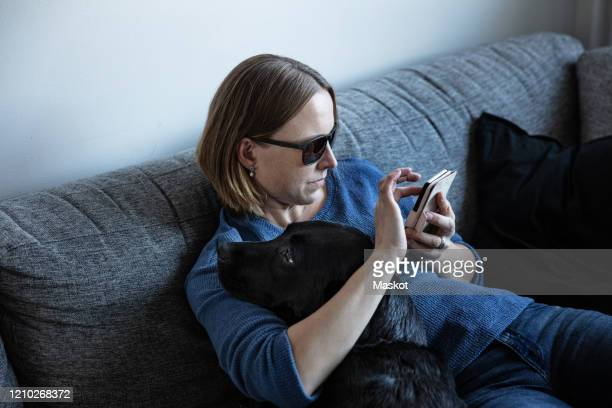 blind woman using smart phone while sitting with dog on sofa at home - disabilitycollection stock-fotos und bilder