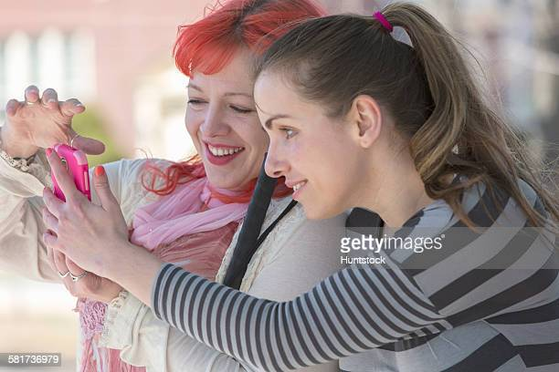 Blind young women using assistive technology on their cell phones