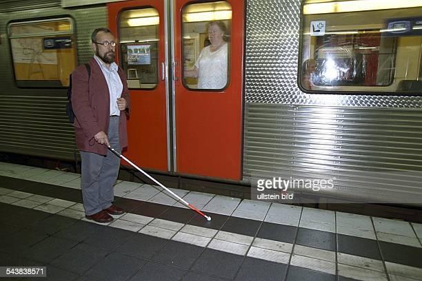 Blinder Fahrgast mit Stock auf einem Bahnsteig der Hamburger UBahn