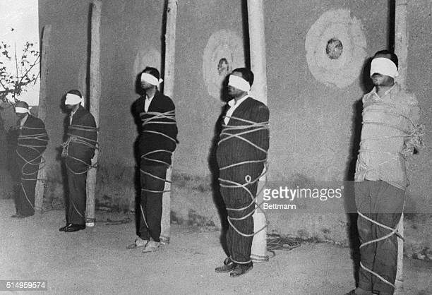 Blindfolded and bound to stakes five of ten alleged Communist spies await death before a firing squad in the Ghasr Army Barracks in Tehran Nine army...