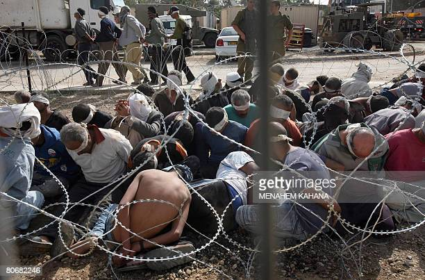 Blindfolded and handcuffed arrested Palestinian men wait inside a militray base on the IsraeliGaza border following an Israeli military operation in...