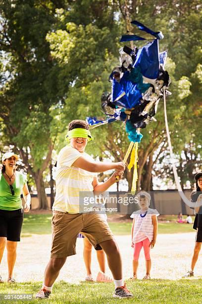 Blindfolded boy hitting pinata at party