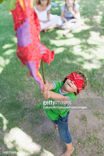 Blindfolded boy with pinata at party