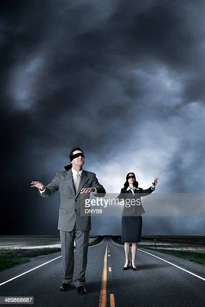 Blindfolded businessman and businesswoman walking in middle of highway