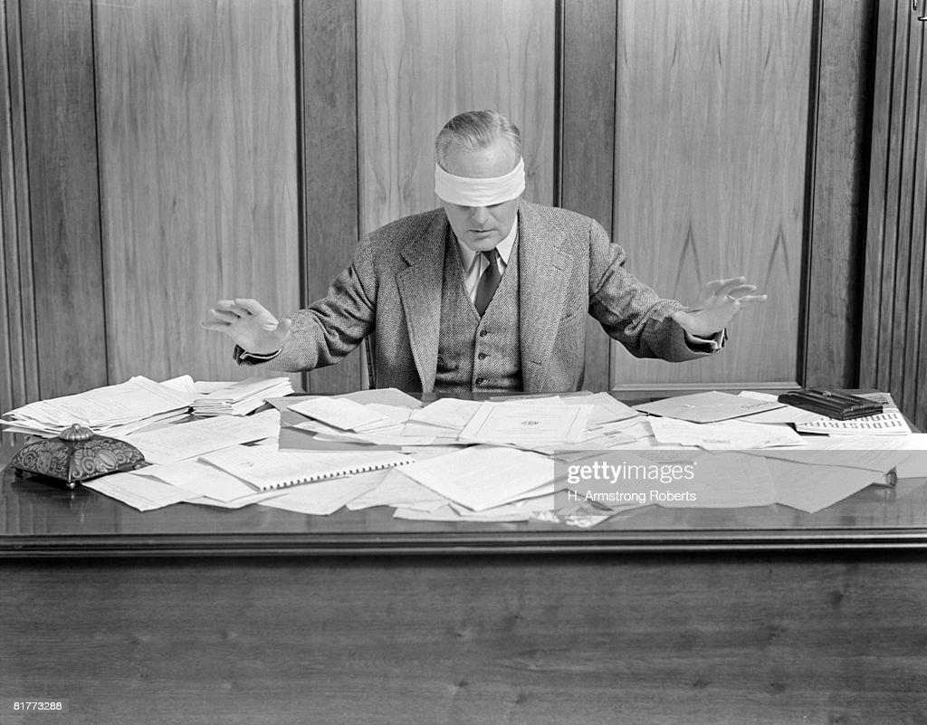 Blindfolded Businessman At Desk Covered With Papers. : Bildbanksbilder