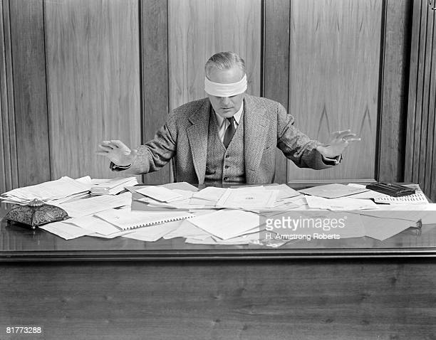 Blindfolded Businessman At Desk Covered With Papers.
