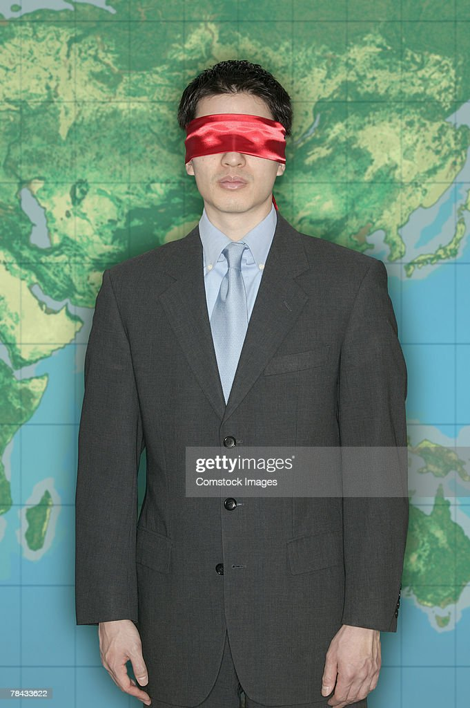 Blindfolded businessman in front of world map : Stockfoto