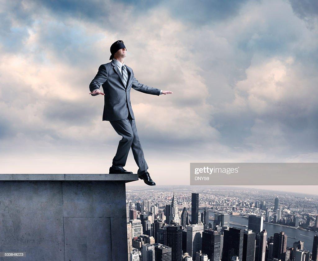 Blindfolded Businessman On Ledge : Stock Photo