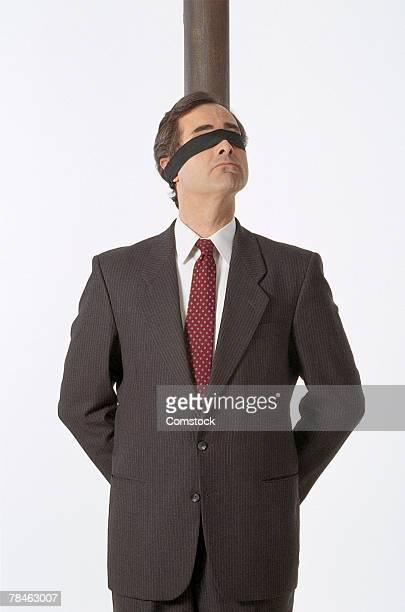 blindfolded businessman tied to pole - vuurpeloton stockfoto's en -beelden