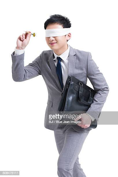 Blindfolded businessman with dart