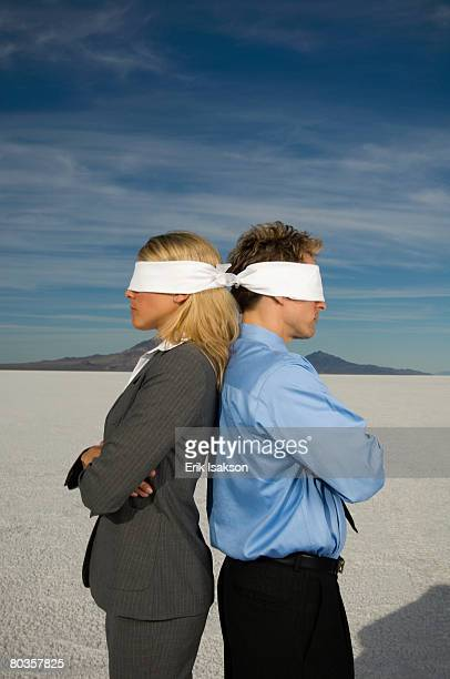 Blindfolded businesspeople standing back to back, Salt Flats, Utah, United States