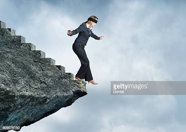 blindfolded businesswoman about to step off stairs - hazard stock pictures, royalty-free photos & images
