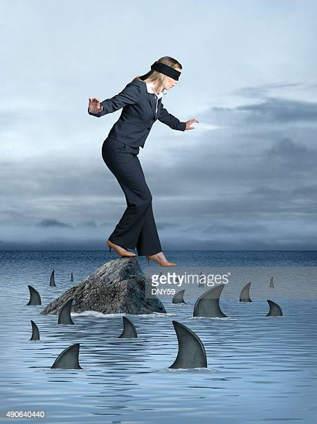 Blindfolded Businesswoman Surrounded by Sharks