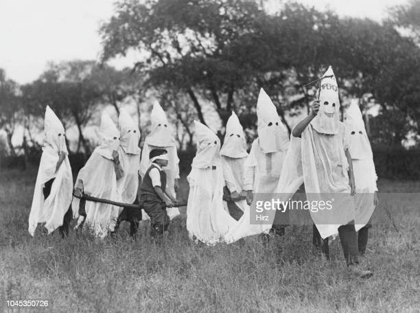 Blindfolded candidate is carried to a secret meeting place by a group of children mimicking the regalia and activities of the Ku Klux Klan, East...