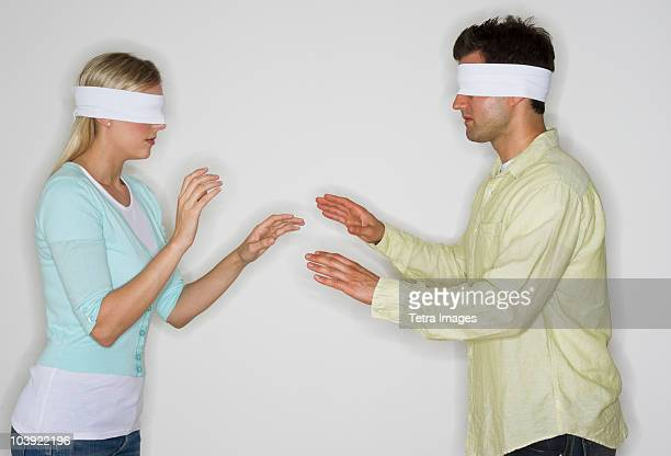 blindfolded couple looking for each other - blindfolded stock photos and pictures