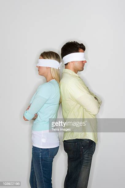 blindfolded couple standing back to back - love is blind stock pictures, royalty-free photos & images