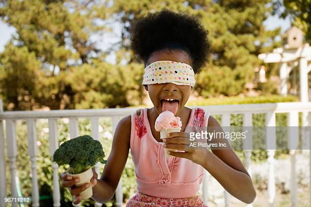 Blindfolded girl licks ice cream
