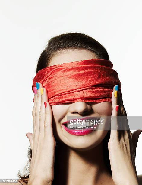 Blindfolded girl with bright nail polish