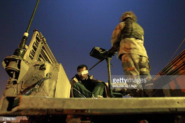 Blindfolded Iraqi detainee awaits inside a Humvee military vehicle during a raid conducted by US soldiers with the 1st Battalion, 22nd Brigade, 4th...