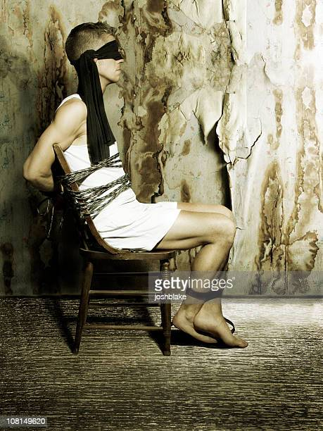 blindfolded man sitting in chair - man tied to chair stock photos and pictures
