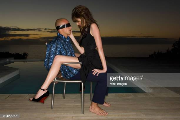 Blindfolded man sitting on a chair beside a swimming pool, a woman sitting on his lap.