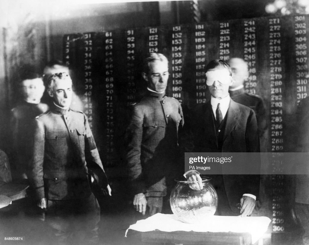 A blindfolded Mr W  Baker, Secretary of War, drawing out