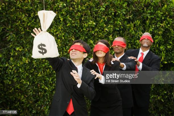 Blindfolded multi-ethnic businesspeople reaching for money