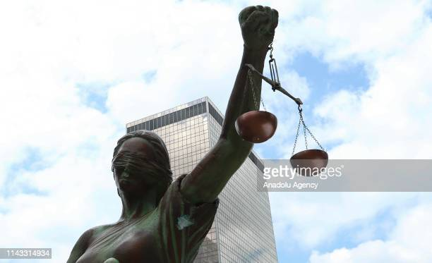 Blindfolded statue of Lady Justice holding scales is seen as environmentalists stage a demonstration to draw attention to global warming and climate...