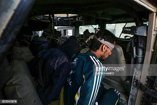 Blindfolded suspected Islamic State group jihadists sit in a Humvee after they were captured by Iraqi forces near the ancient town of Nimrud located...