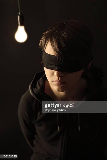 Blindfolded adolescent être retenu en otage dans une chambre noire