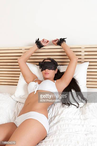 blindfolded woman in lingerie on a bed - sadomasoquismo fotografías e imágenes de stock