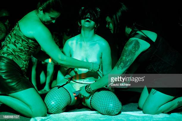 A blindfolded woman laughs as she receives an electric shock to her inner thigh and clothespins to her breasts as she voluntarily competes in a...